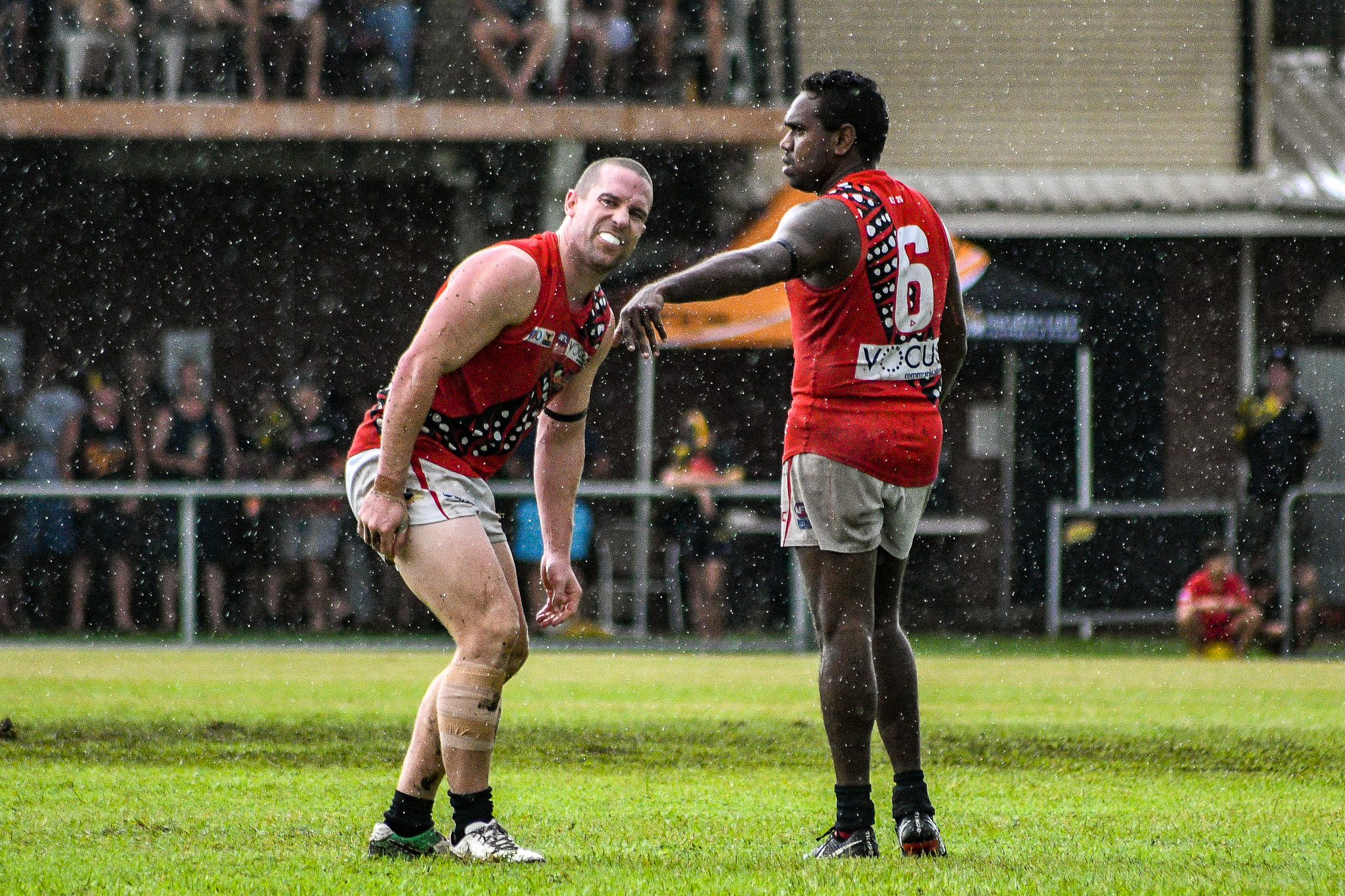 Hams limps after copping a knock against Nightcliff. Skipper Paddy Heenan looks unconcerned.