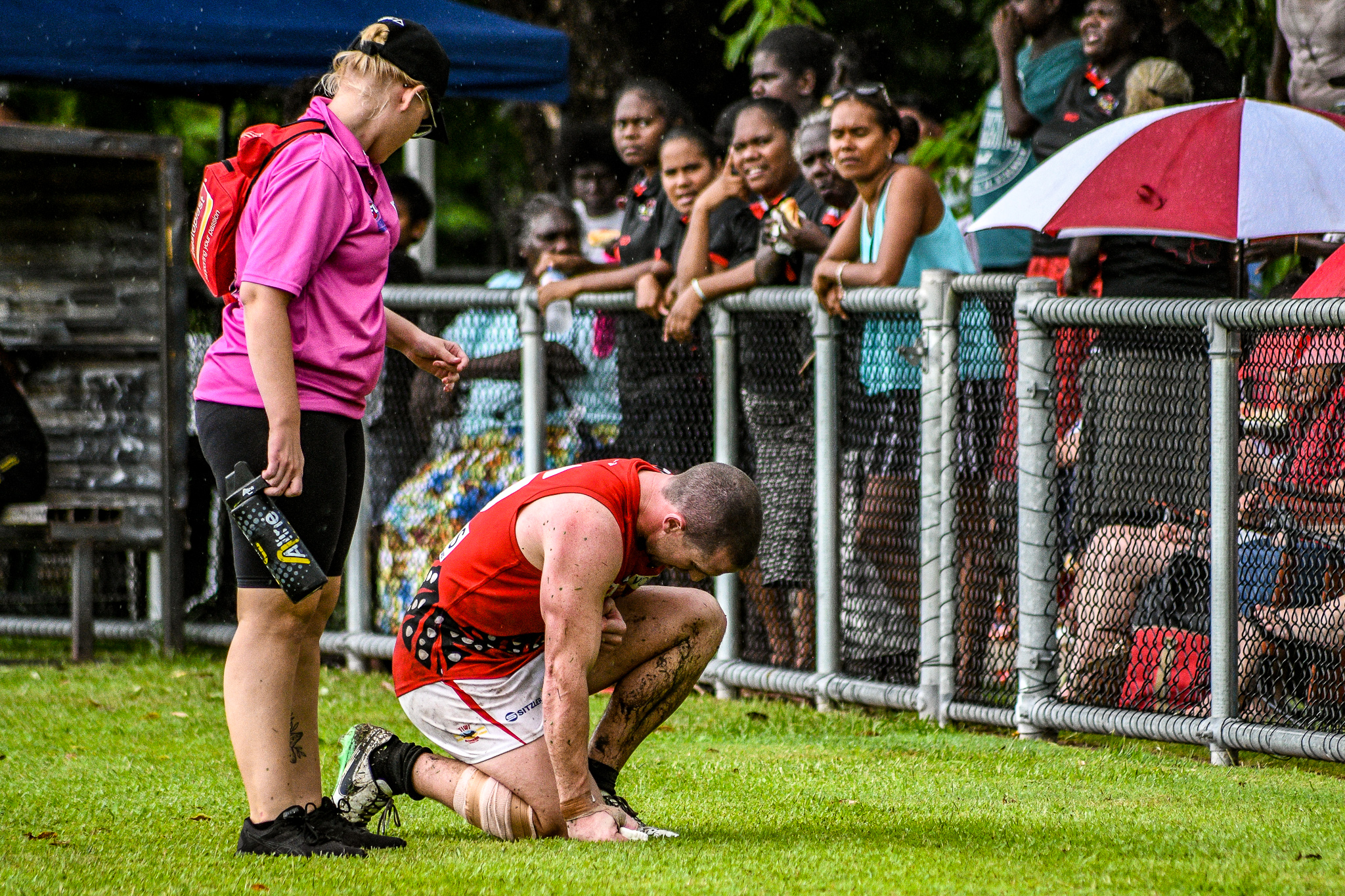 Bombers trainer Shileigh Martin is called upon (again) to treat Hams as he struggles toward the bench against Nightcliff