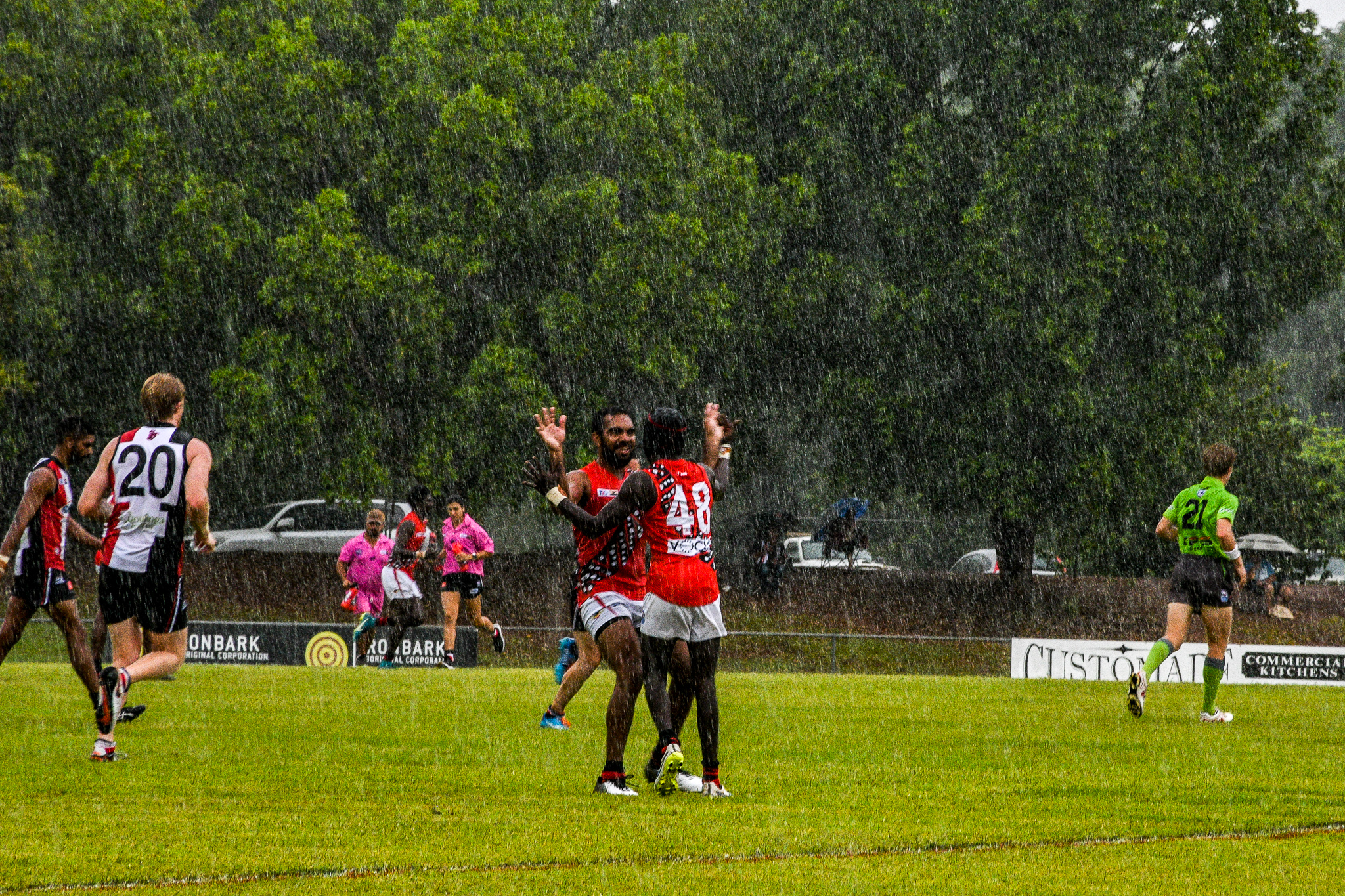 Yolgnu man Nathan Djerrkura –who played 25 games for the Cats and the Dogs in the AFL – celebrates with Harley Puruntatameri (number 48) in the rain. Tiwi Bombers v Southern Crocs, NTFL round 14, January 19, 2019.