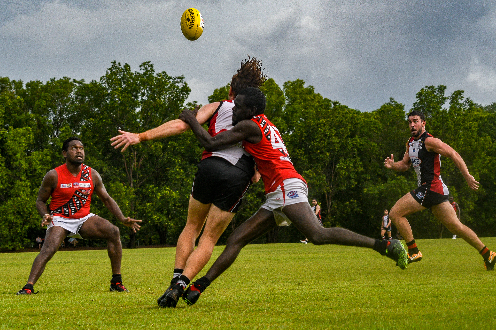 Randy Mungatopi runs his opponent down, and Bombers captain Paddy Heenan watches the ball fly over his head. Tiwi Bombers v Southern Crocs, NTFL round 14, January 19, 2019.
