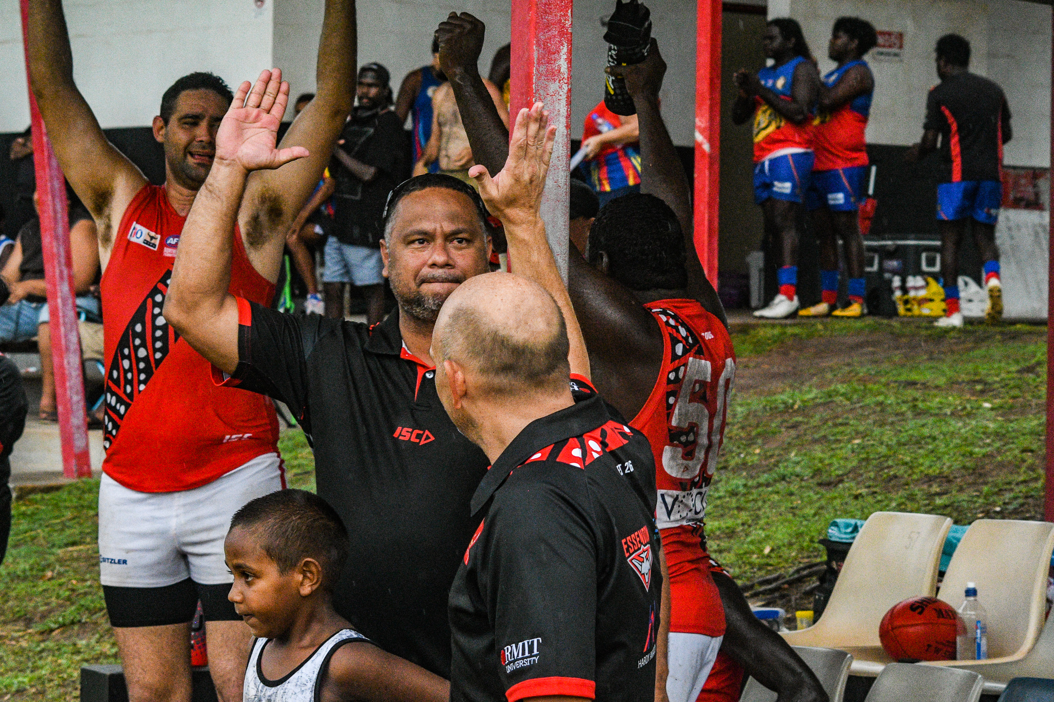 """Bombers assistant coach Jeffrey """"Yello"""" Simon high fives Brenton Toy after the final siren against the Crocs. """"Yello"""" is a vocalist and guitarist for popular saltwater Tiwi band B2M. Tiwi Bombers v Southern Crocs, NTFL round 14, January 19, 2019."""