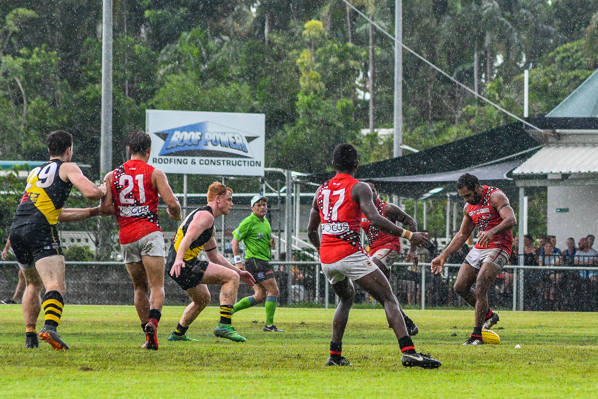Nathan Djerrkura tries to quickly kick the wet ball out of congestion, but it slips, and he ends up having a fresh airy. Tiwi Bombers v Nightcliff Tigers, NTFL round 15, January 27, 2019.
