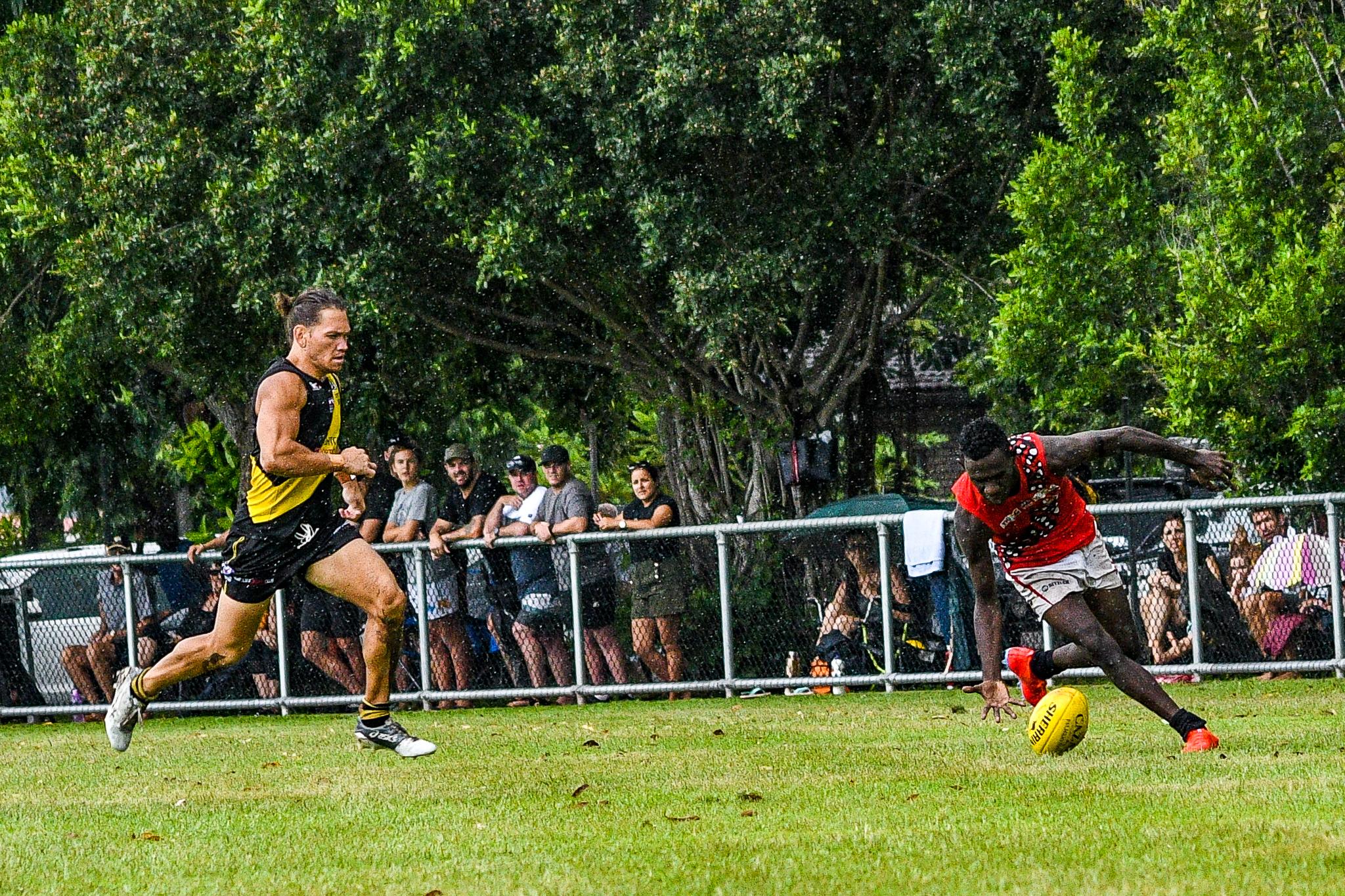 Dion Munkara stoops to pick up a wet ball…Tiwi Bombers v Nightcliff Tigers, NTFL round 15, January 27, 2019.
