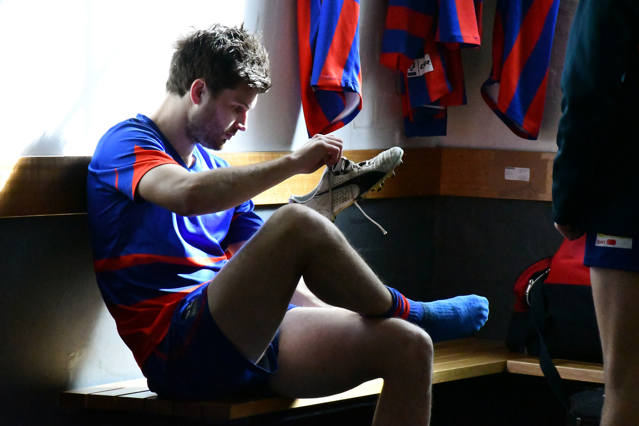 Player Dylan Van Unen slides on his boots in the club change rooms before the game against Collingwood on 11th August 2018.