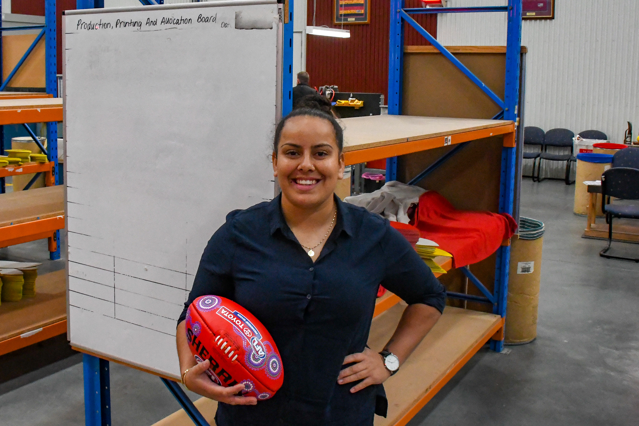 Artist Rheanna Lotter with the Sherrin footballs she designed especially for the AFL's Sir Doug Nicholls Round
