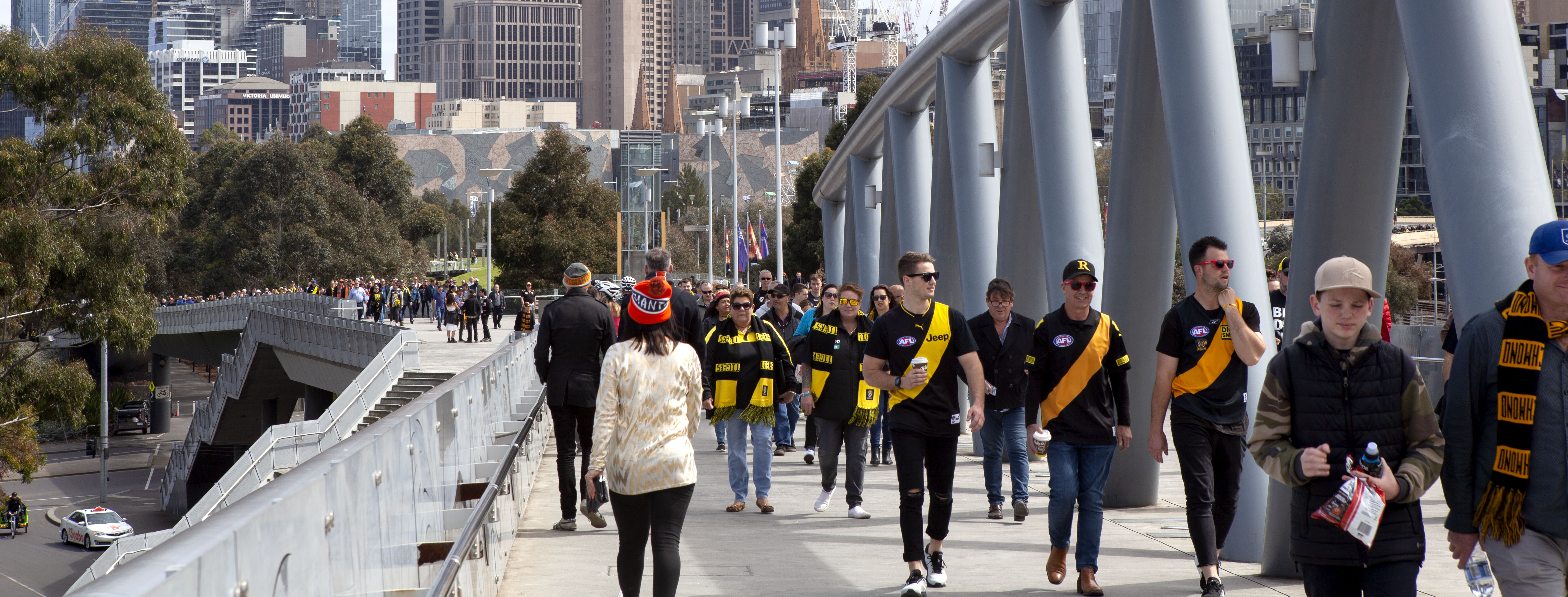 A lonely Giants fan walks amongst the sea of yellow and black heading to the MCG to watch the AFL Grand Final.