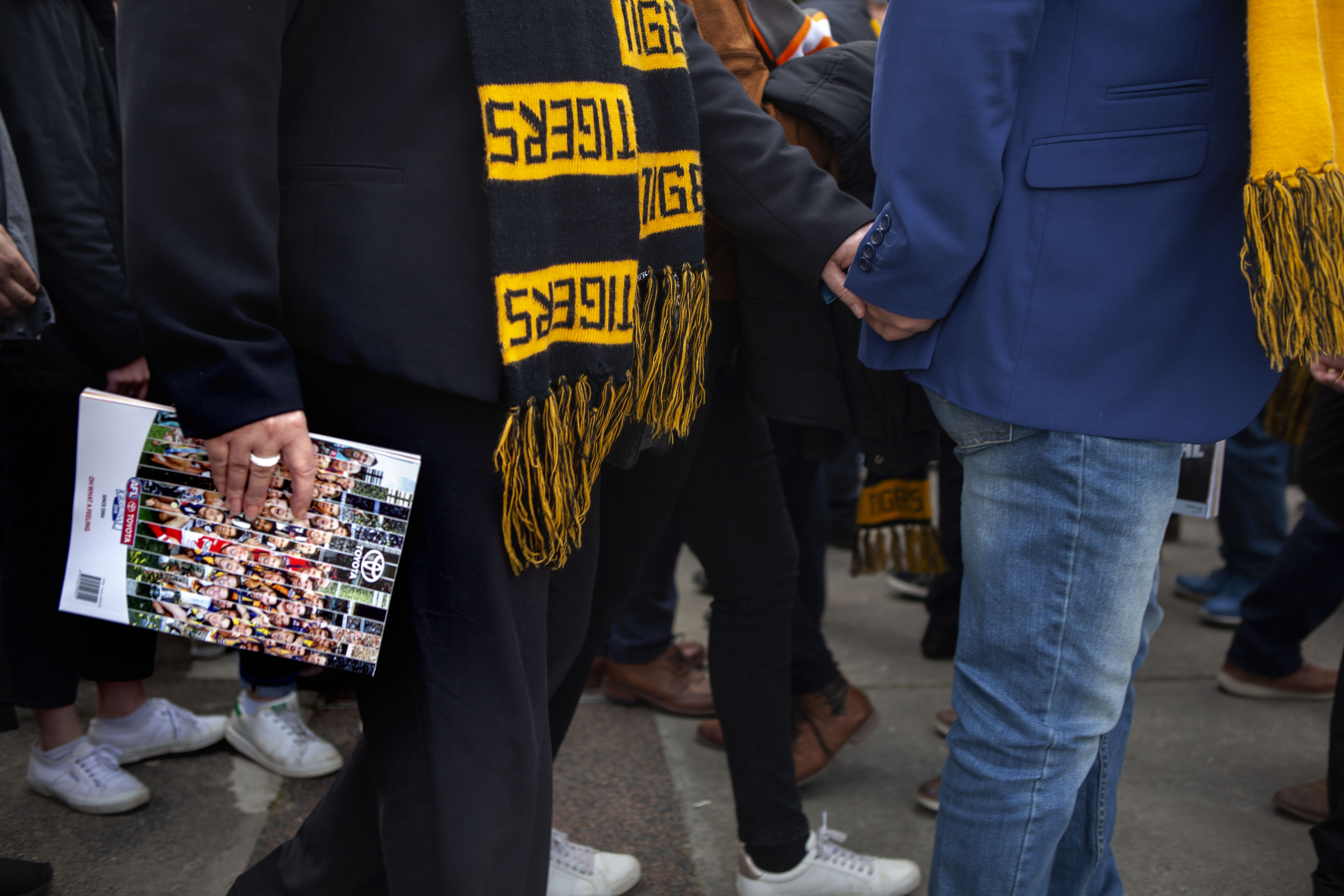 Most people entering the stadium are holding a copy of the famous Footy Record.