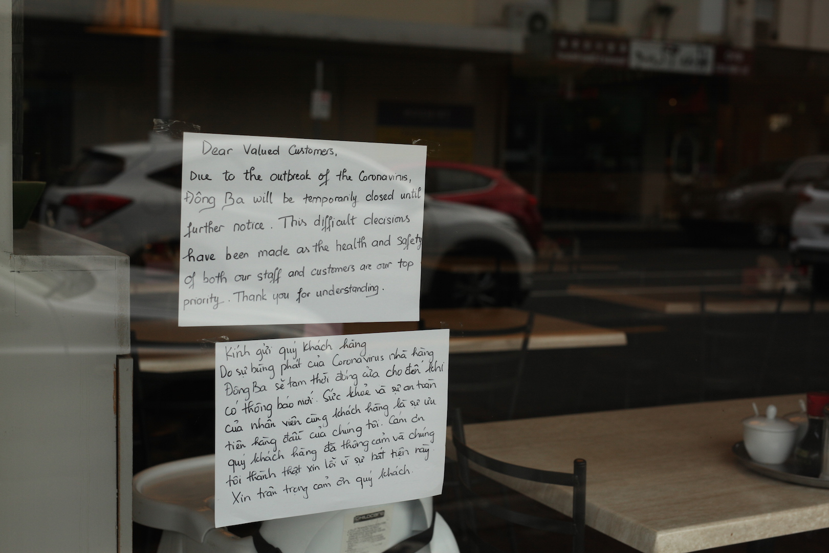 Messages like these, posted on the window of a Footscray Vietnamese eatery, are appearing in windows along the normally lively Footscray shopping precinct.